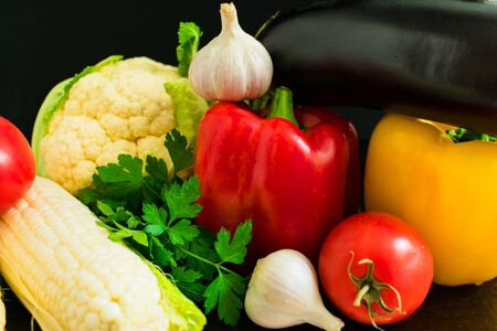Vegetables on a black background. Organic food and fresh vegetables. Seaweed, pepper, eggplant, parsley, garlic, corn, and tomato close-up. 스톡 콘텐츠