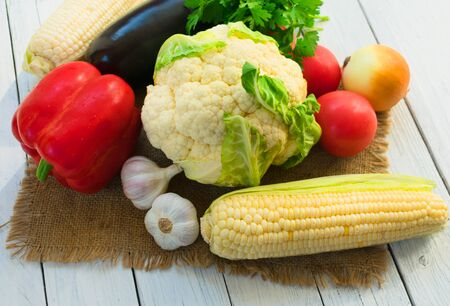 Vegetables on a wooden white background. Organic food and fresh vegetables. Cauliflower, peppers, eggplant, parsley, garlic, corn and tomatoes. Close-up.