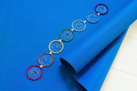 Blue yoga mat and seven chakra decoration. Yoga concept.