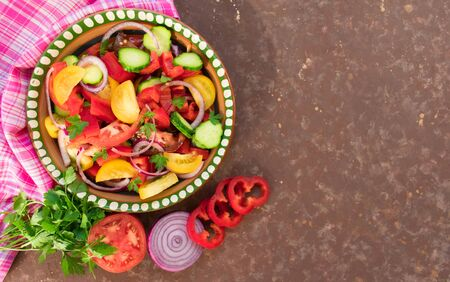 Salad of tomato, pepper, cucumber, onion, herbs. Homemade food. The concept of tasty and healthy food. Dark brown background. Top view. Copy space.