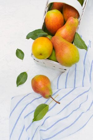 Fresh organic pears in a white basket on a white wooden background. Top view.