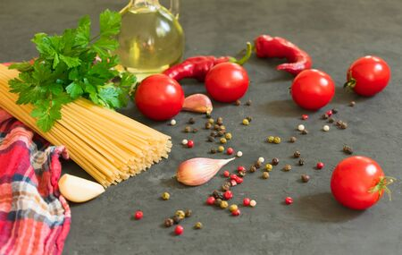 Ingredients for cooking spaghetti - raw spaghetti, cherry tomatoes, chili peppers, garlic, herbs, spices and olive oil on a black background. Culinary background. Selective focus. 写真素材