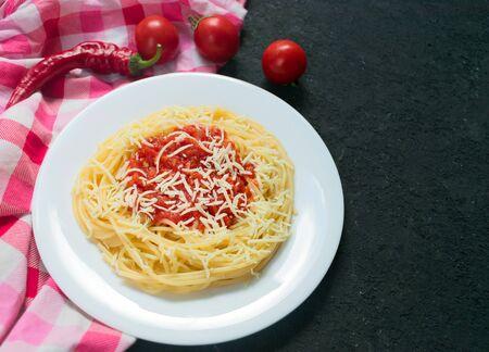 Pasta con salsa di pomodoro piccante, parmigiano. Pasta Chiffery Rigati su sfondo nero. Copia spazio. Vista dall'alto.