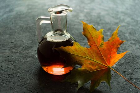 Bottle with maple syrup and maple leaf on a black background.