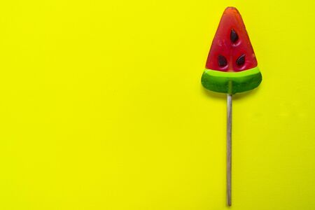 Watermelon wedge lollipop on bright yellow background. Copy space.