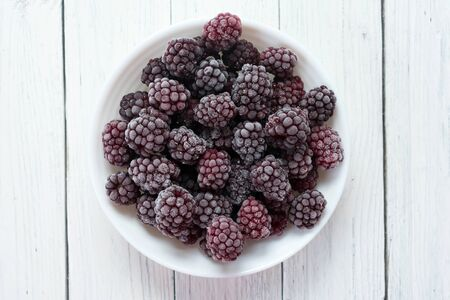 Frozen blackberries in a plate on a wooden white background. Top view. Standard-Bild