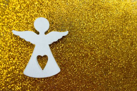 Wooden figurine of a little white angel on a shiny golden background. Copy space. Christmas holiday concept.