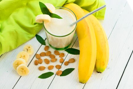 Banana smoothie with almond milk. Milk smoothie with bananas and almonds on a white wooden table. The concept of vegetarian products. Top view. Reklamní fotografie