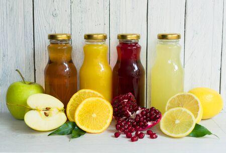Four types of juice (pomegranate, apple, lemon, orange juice) in glass bottles on a white wooden background.