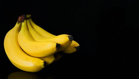 Bananas are isolated on a black background. Copy space. Reklamní fotografie