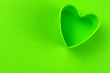 Green heart shape on green background. Copy space.