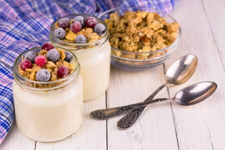 Two portions of fresh yogurt with frozen berries and granola on a whit Stock Photo