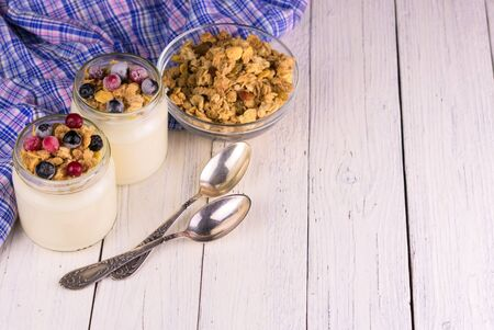 Two jars of fresh yogurt with frozen berries and granola on a white wooden table. Copy space. Stock Photo