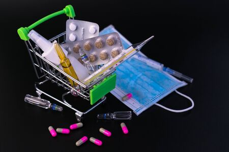 Small supermarket cart with pills, ampoules, thermometer, medical mask on a black background. Concept of protection against viral diseases, quarantine. Stock fotó
