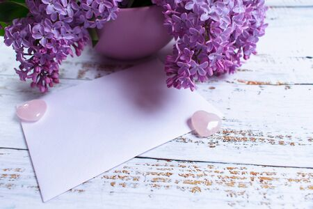 A bouquet of lilac flowers in a lilac vase and an envelope. Postcard. Copy space