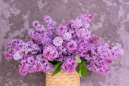 Beautiful bouquet of purple lilac in a vase on a background of a gray wall.Close-up. Фото со стока