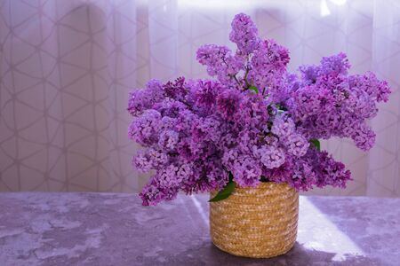 Bouquet of lilacs in a basket on a table against a window background. Copy space.