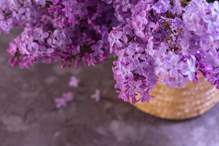 Delicate bouquet of purple lilac in a basket on a gray table. Close-up. Selective focus. View from above. Фото со стока