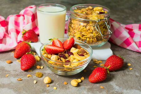 Healthy granola breakfast with nuts and fresh strawberries. Close-up.