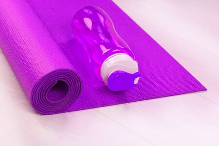 Sports concept. Pink bottle of water and yoga mat.