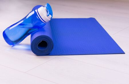 Sports concept. Blue water bottle and yoga mat. Copy space.