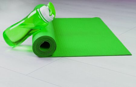 Yoga mat and green bottle of water. Copy space.