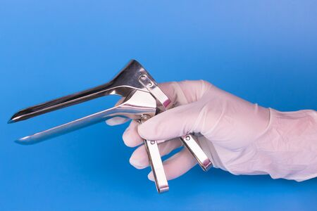 Gynecological mirror in the hand of a doctor on a blue background. Medical tool. Stock Photo