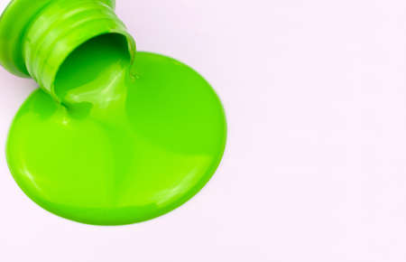 Green paint spills from a bottle on a white background.Copy space. Foto de archivo