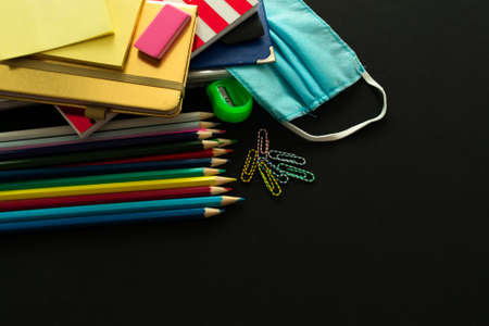 School supplies and medical mask, school opening, return to school after COVID-19 pandemic, new normal concept. Copy space.