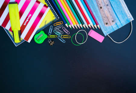 School supplies and medical mask on a blue background, returning to school after the COVID-19 pandemic. Copy space.