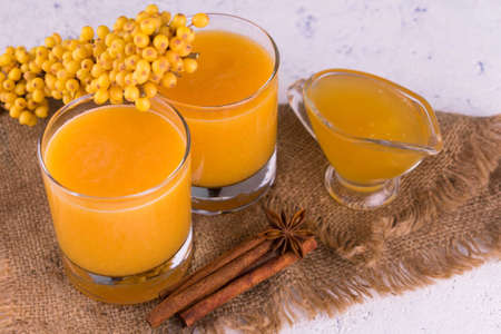 Two glasses with sea buckthorn, honey and cinnamon fruit drink.