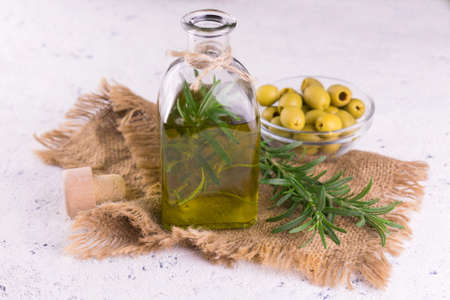 A bottle of olive oil with a branch of rosemary in the inside on a white background. Close-up. 免版税图像
