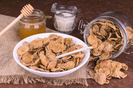 Whole grain breakfast cereals with honey and nuts in a plate on a brown background.