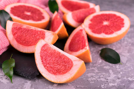 Slices of grapefruit on a gray background. Close-up.