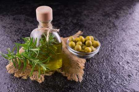 Olive oil in a bottle on a black background and a sprig of rosemary.