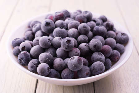Frozen blueberries in a white plate on a white wooden background.