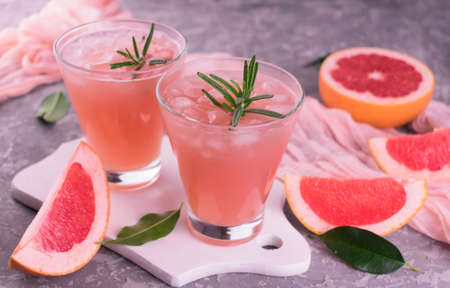 Cocktail with grapefruit and rosemary. Refreshing drink with ice.