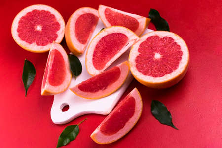 Grapefruit and wedges with leaves, on a red background. View from above. Flat lay.