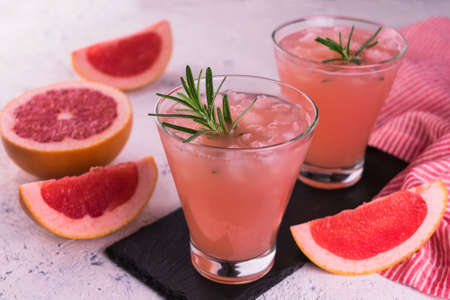 Cocktail with grapefruit juice and rosemary on a white background. Close-up.