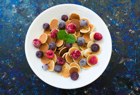 Plate with mini pancakes and berries on a dark blue background. Flat lay. Stock fotó