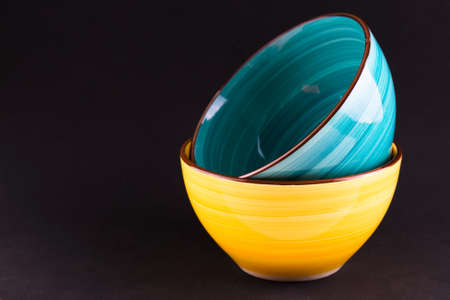 Two yellow and blue ceramic bowls on a black background.Copy space. Stock fotó