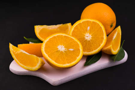 Sliced oranges on a white wooden board on a black background. Close-up.