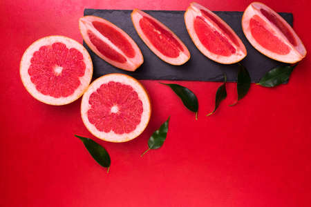 Grapefruit slices on a black slate board on a red background. Copy space. Copy space.