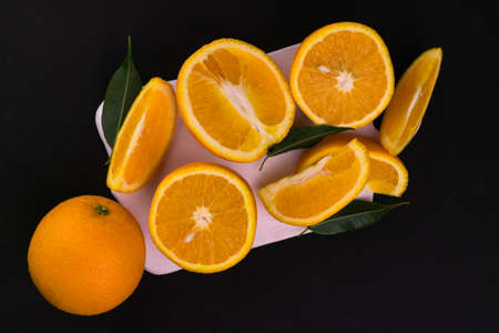 Oranges on a white wooden board on a black background. Flat lei.