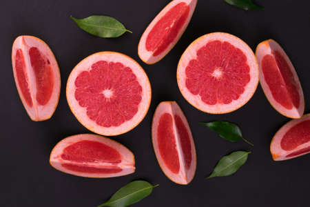 Sliced grapefruit on a black background. Flat lay.