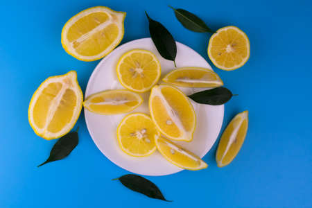 Sliced lemons on a white plate on a light blue background. Top view.