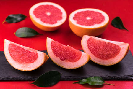 Slices of grapefruit on a black slate board on a red background. Close-up.