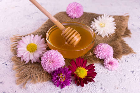 Fresh floral honey and flowers on a white background.