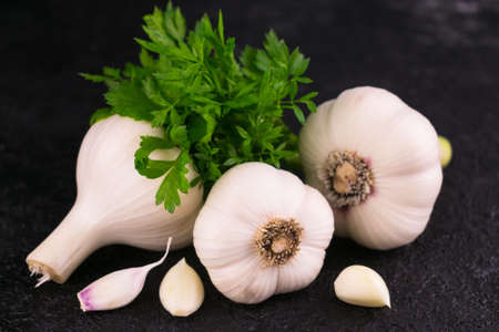 Three garlic and parsley on a black background. Close-up.