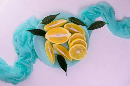 Sliced lemons on a blue plate on a white background. Flat lei.